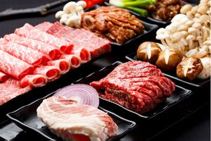 Collection of sliced meat for barbecue on black plates with raw mushrooms