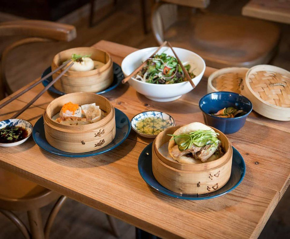 three steamer baskets on a wooden table. The baskets are open and have assorted dim sum items in them like bao and wontons. there is a white bowl with salad and two chopsticks on top of it behind the baskets
