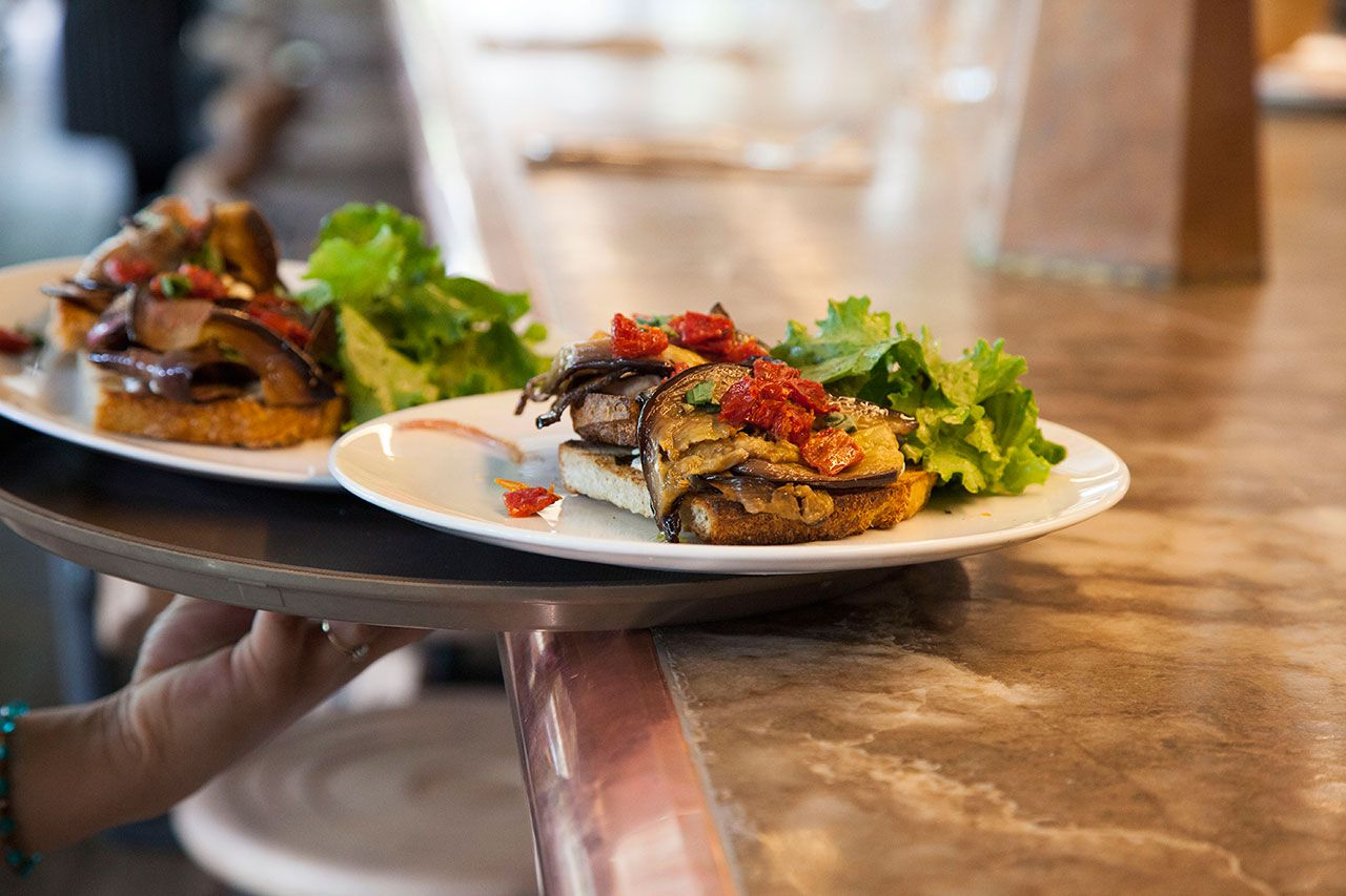 Two servings of grilled peppers and eggplant on toast on a serving tray with a hand holding it