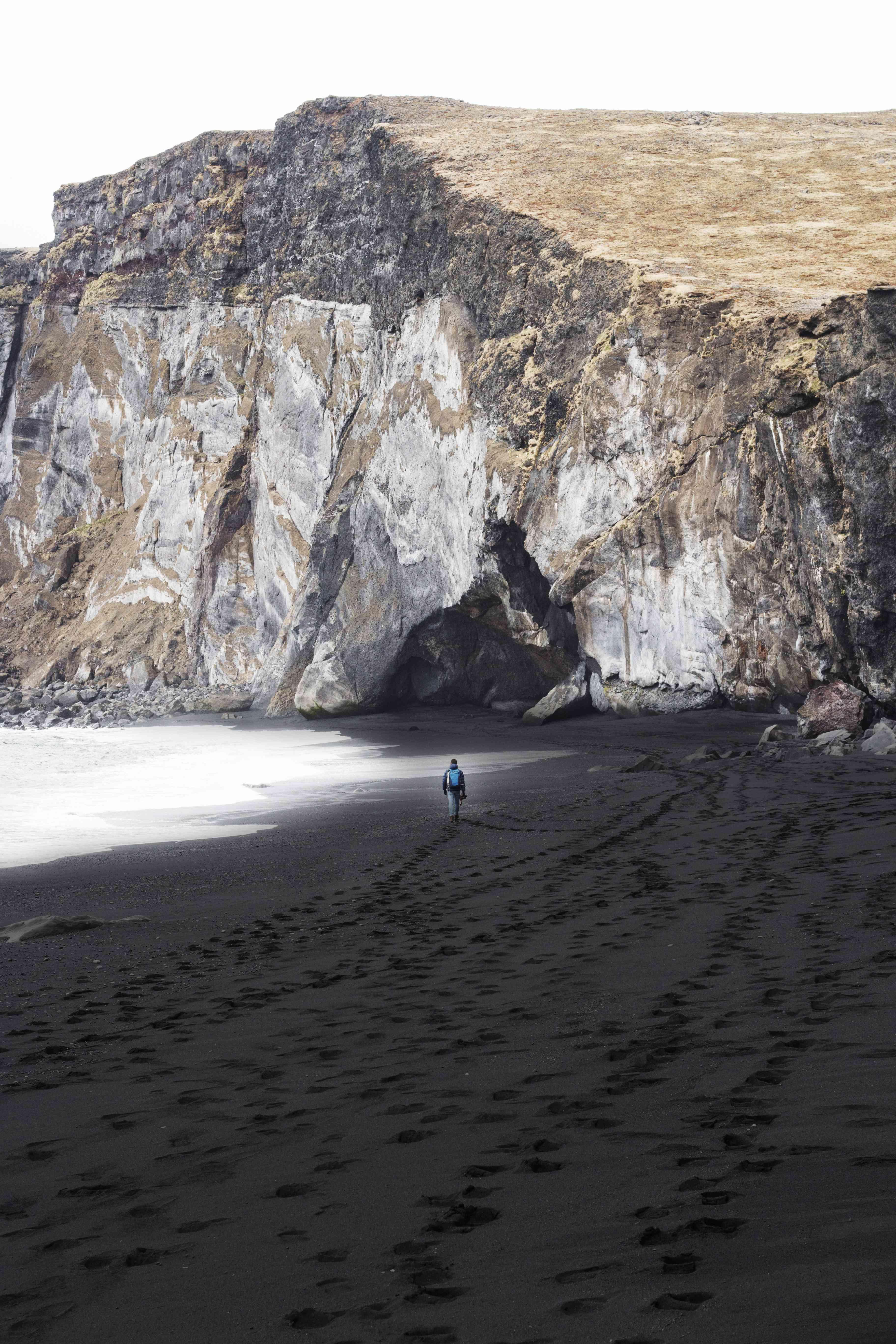 man walking down a black sand beach in Reynisfjara