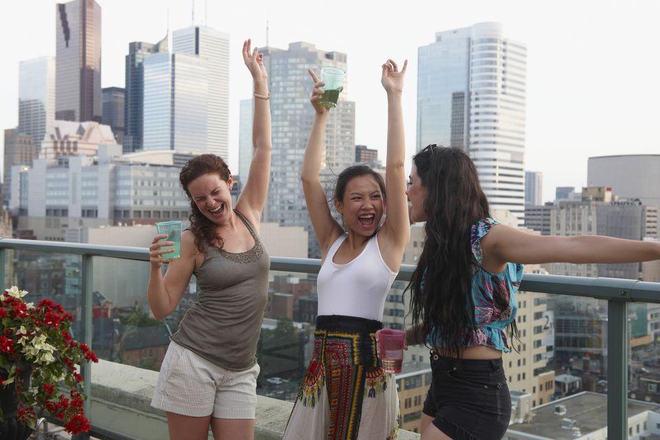Women enjoying cocktails on urban rooftop