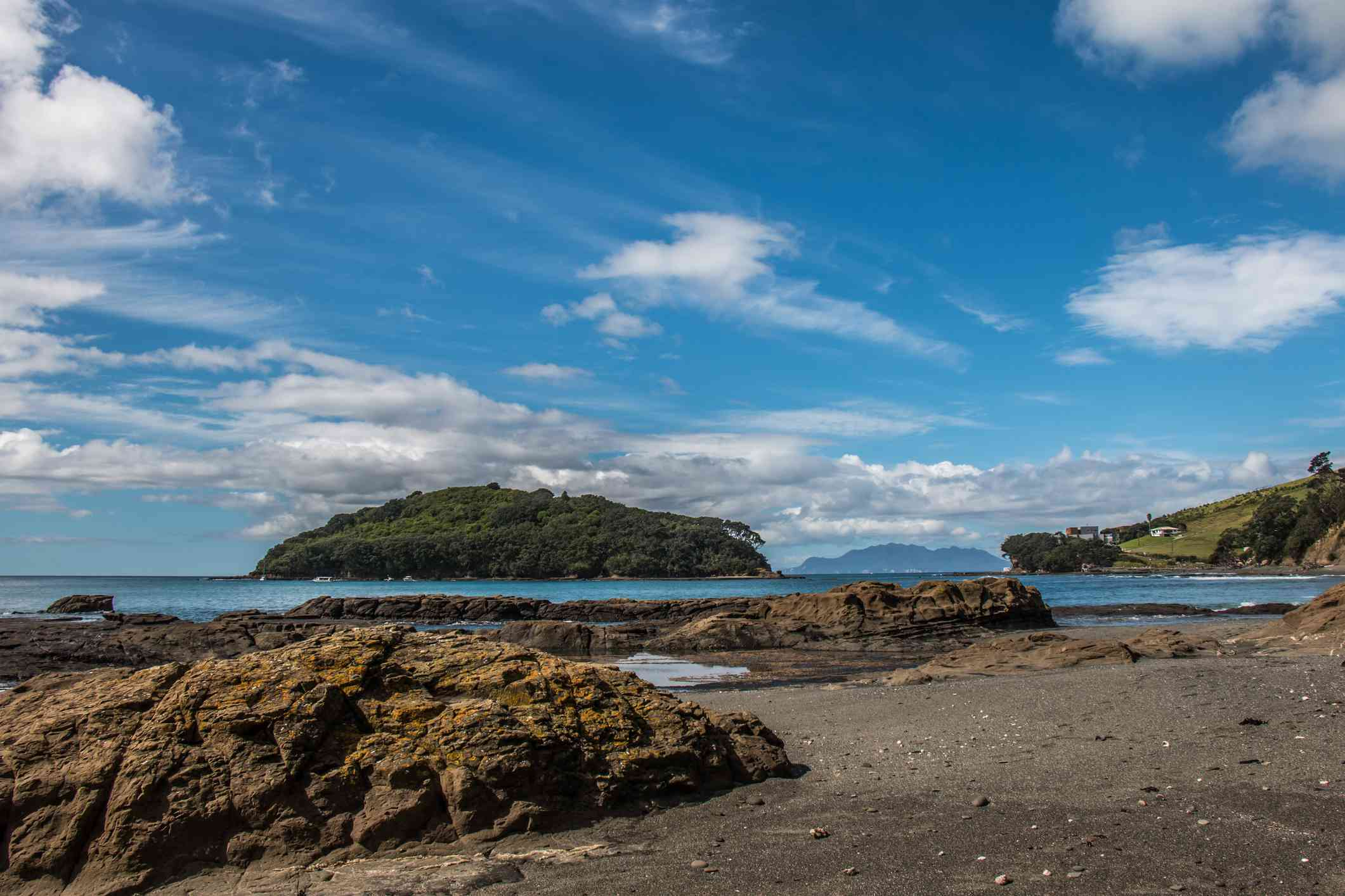 rocky beach with a view of a lush islandand blue sky