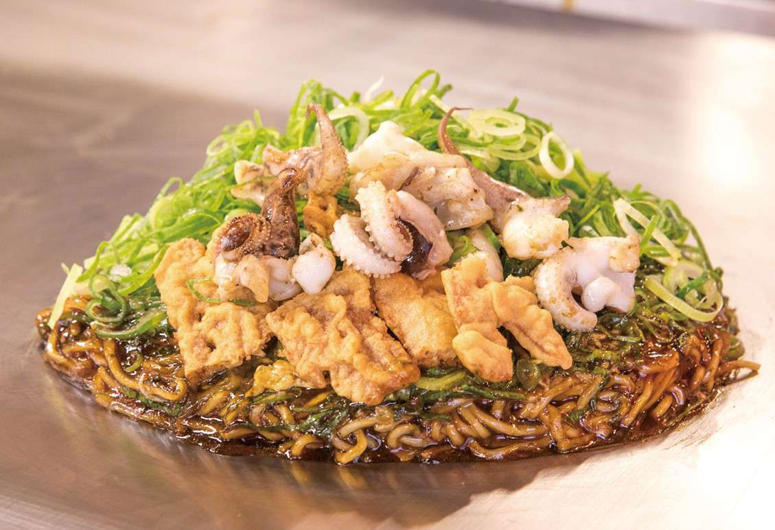 okonomiyaki on a metal table and topped with squid, octopus, and sliced scallions