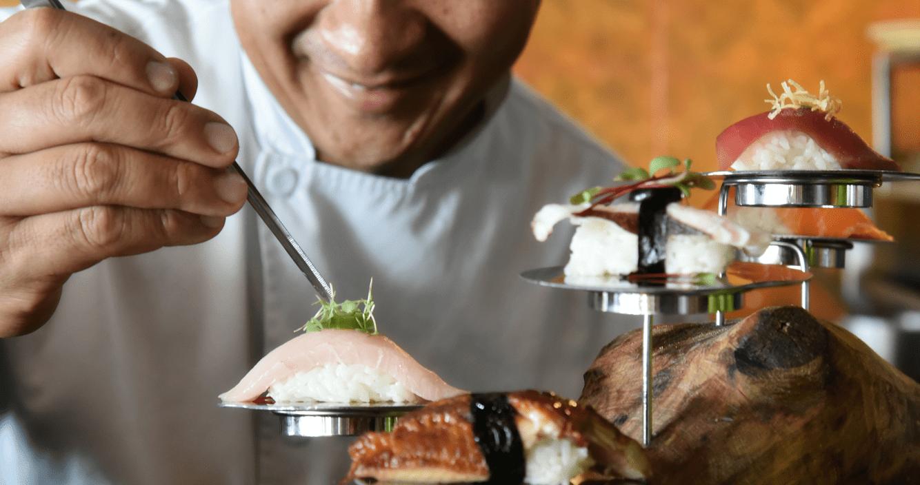Chef adding garnished to nigiri sushi at Tora Mexico in Cancun