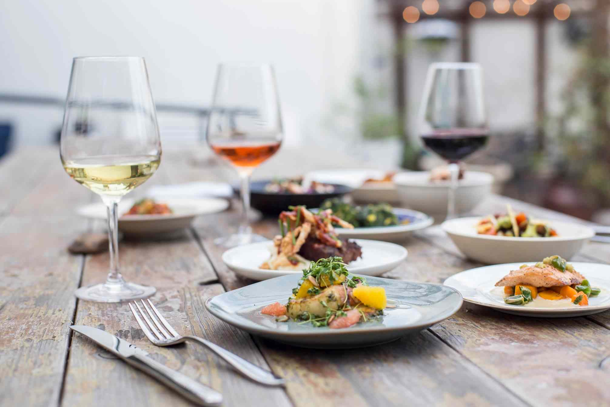 Multiple glasses of wine and plates of food on a wooden table at Cafe Josie