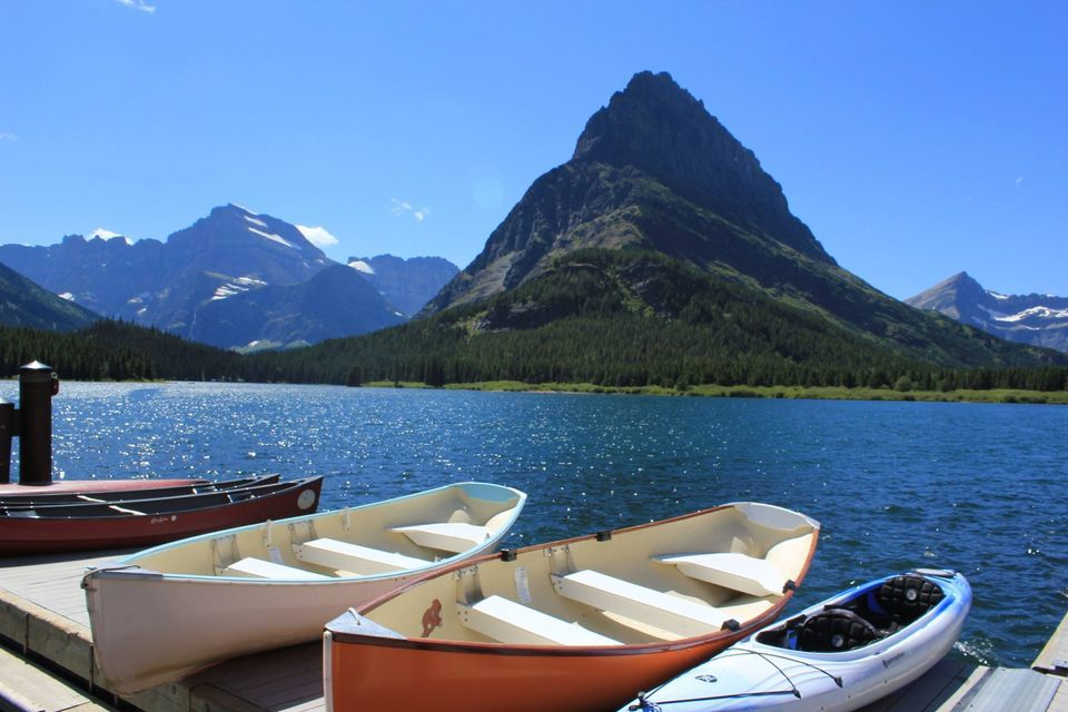 two rowboats, a kayak, and two canoes on a short pier with a mountain in the distance