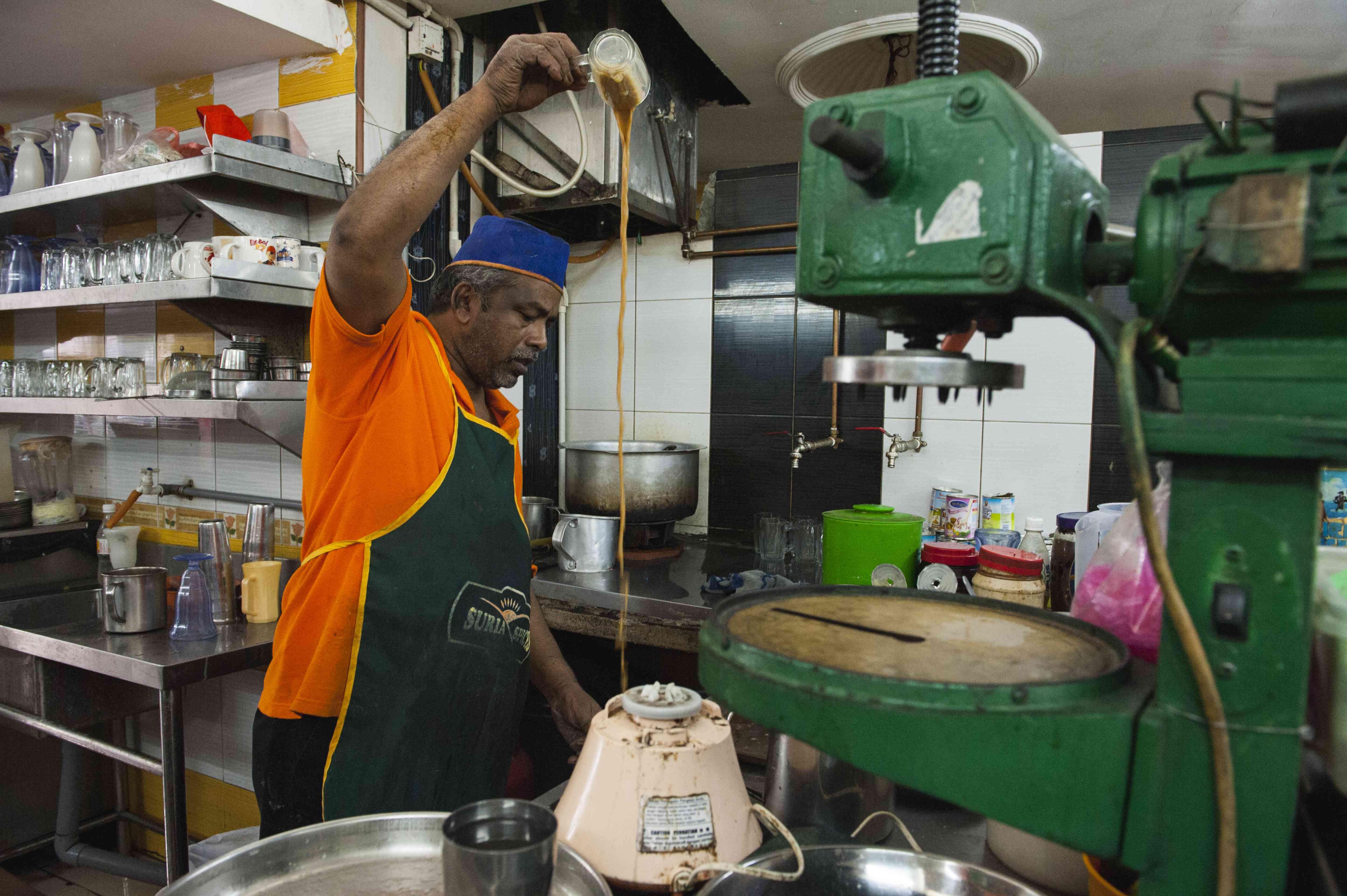Man at a Mamak stall pours teh tarik through the air