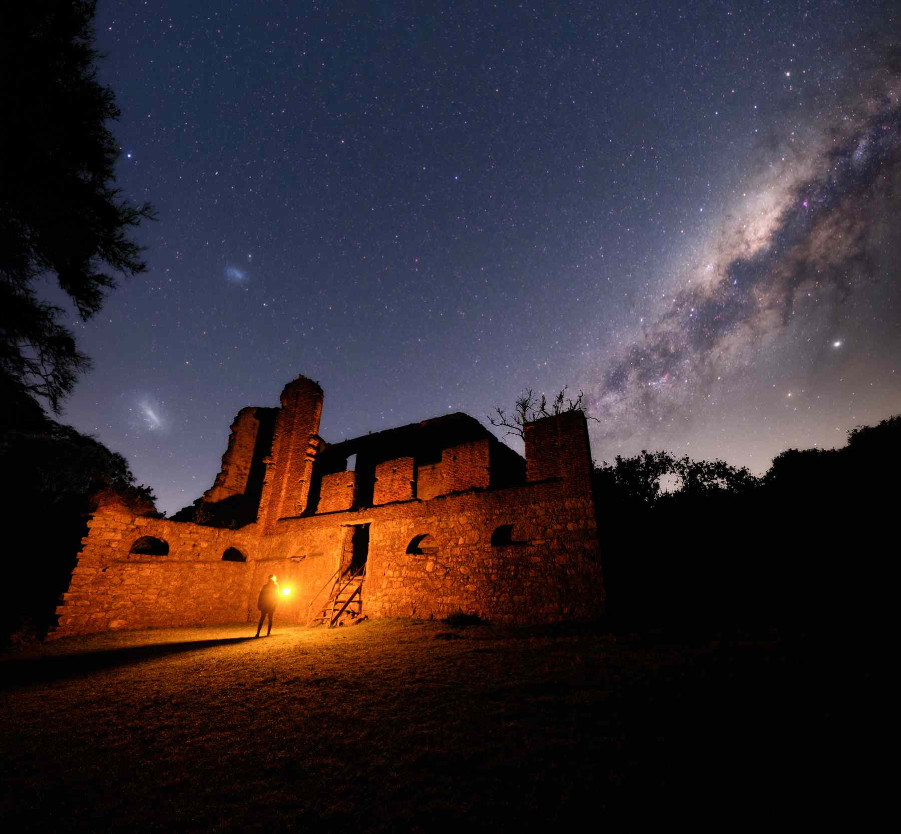 person holding a light standing in the ruins of a stone building with a starry sky overhead