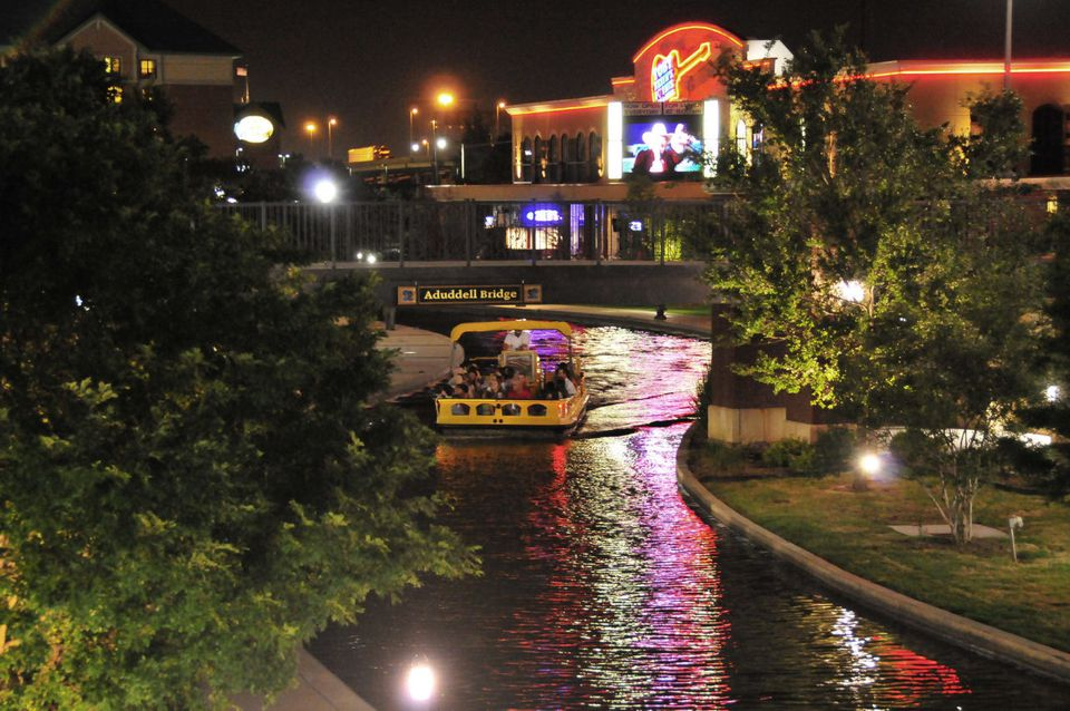 A boat crusing down the canal in bricktown Oklahoma City