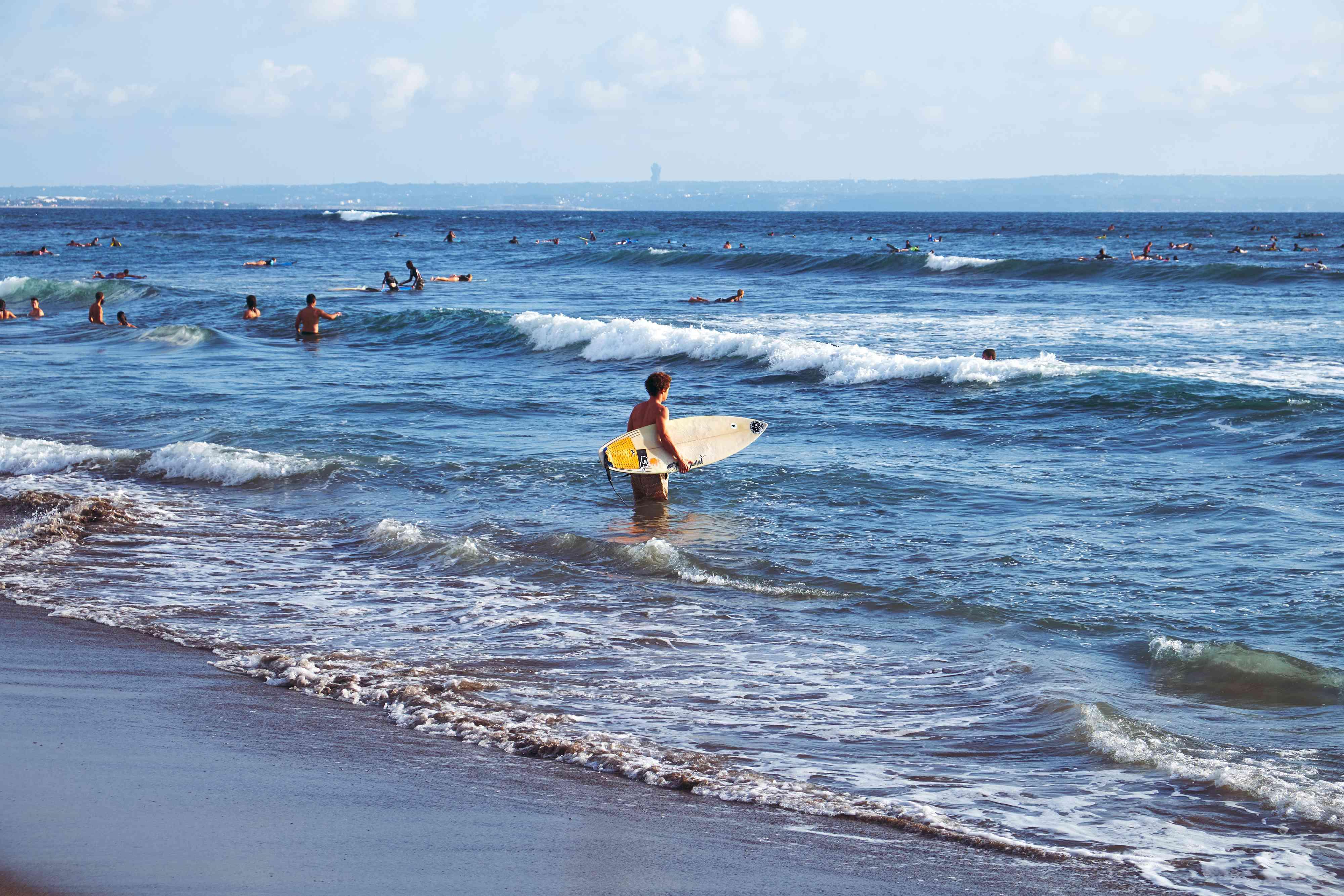 People surfing in the ocean. ??li, Indonesia