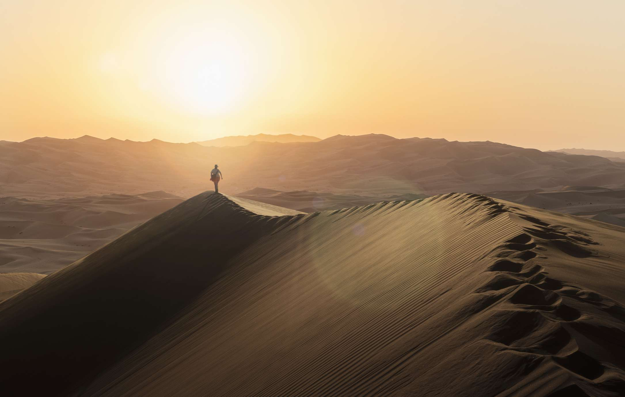 One person walking along the top of a sand dune photographed at sunset