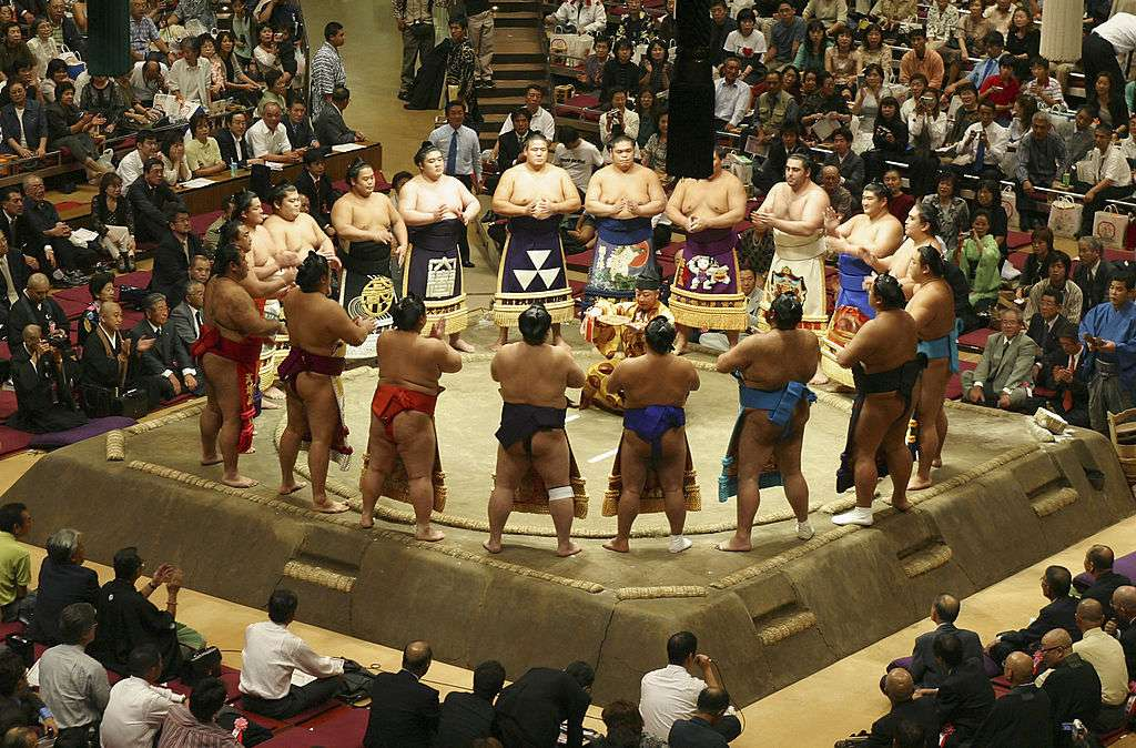 sumo wrestling match where the wrestlers are standing in a circle around the ring
