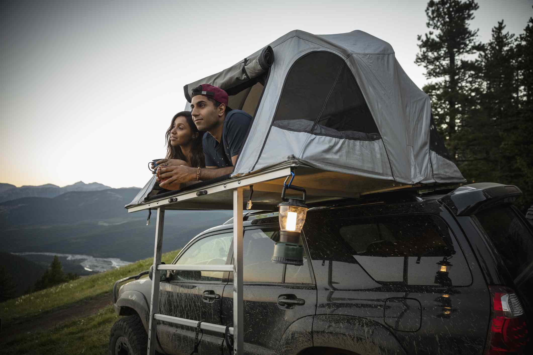 Two people in a car tent on top of a vehicle