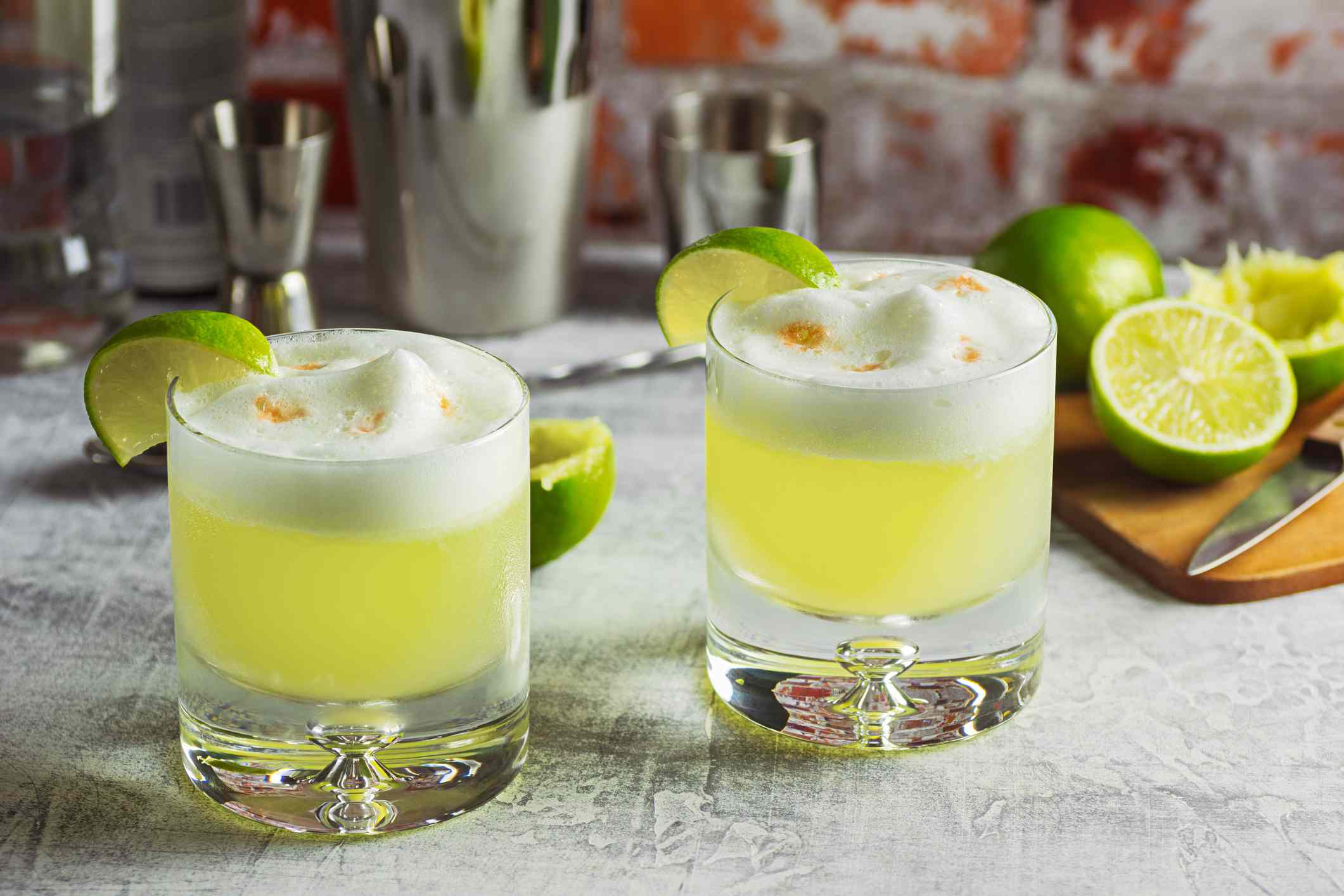 Two Pisco Sour Cocktails on the Bar with Ingredients