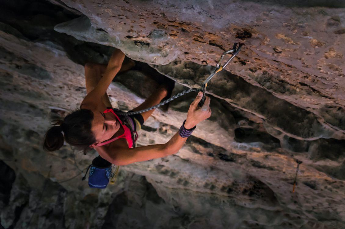 A woman rock climber ascends a limestone rock face.