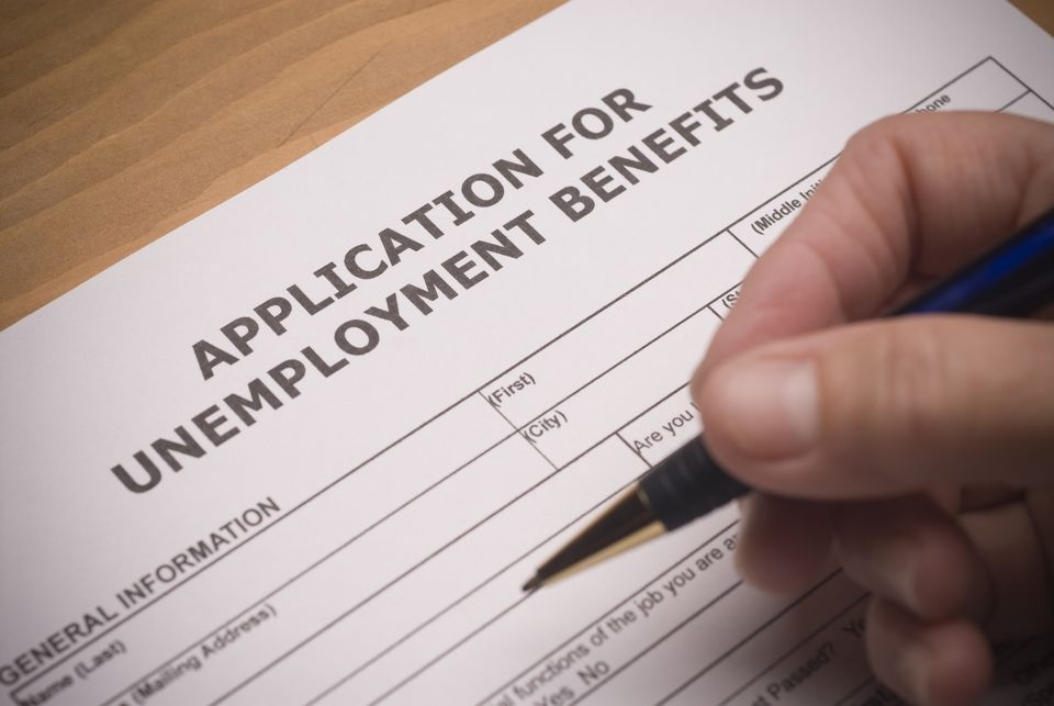 Unemployment benefits form and hand holding pen