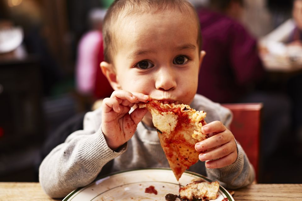Boy eating pizza in NYC restaurant