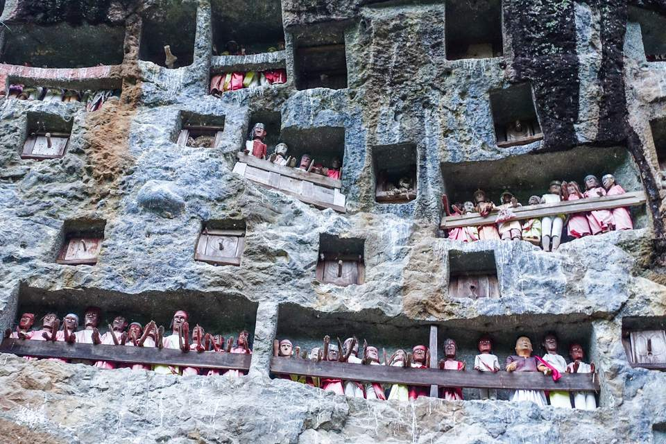 Tau-tau staring out from a limestone cliff at Lemo, Toraja, Indonesia