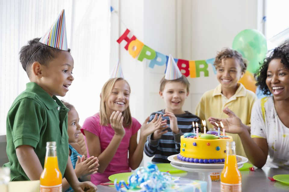 Excited boy blowing out birthday candles at party with family and friends