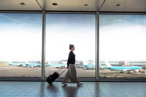 woman with suitcase walking in airport