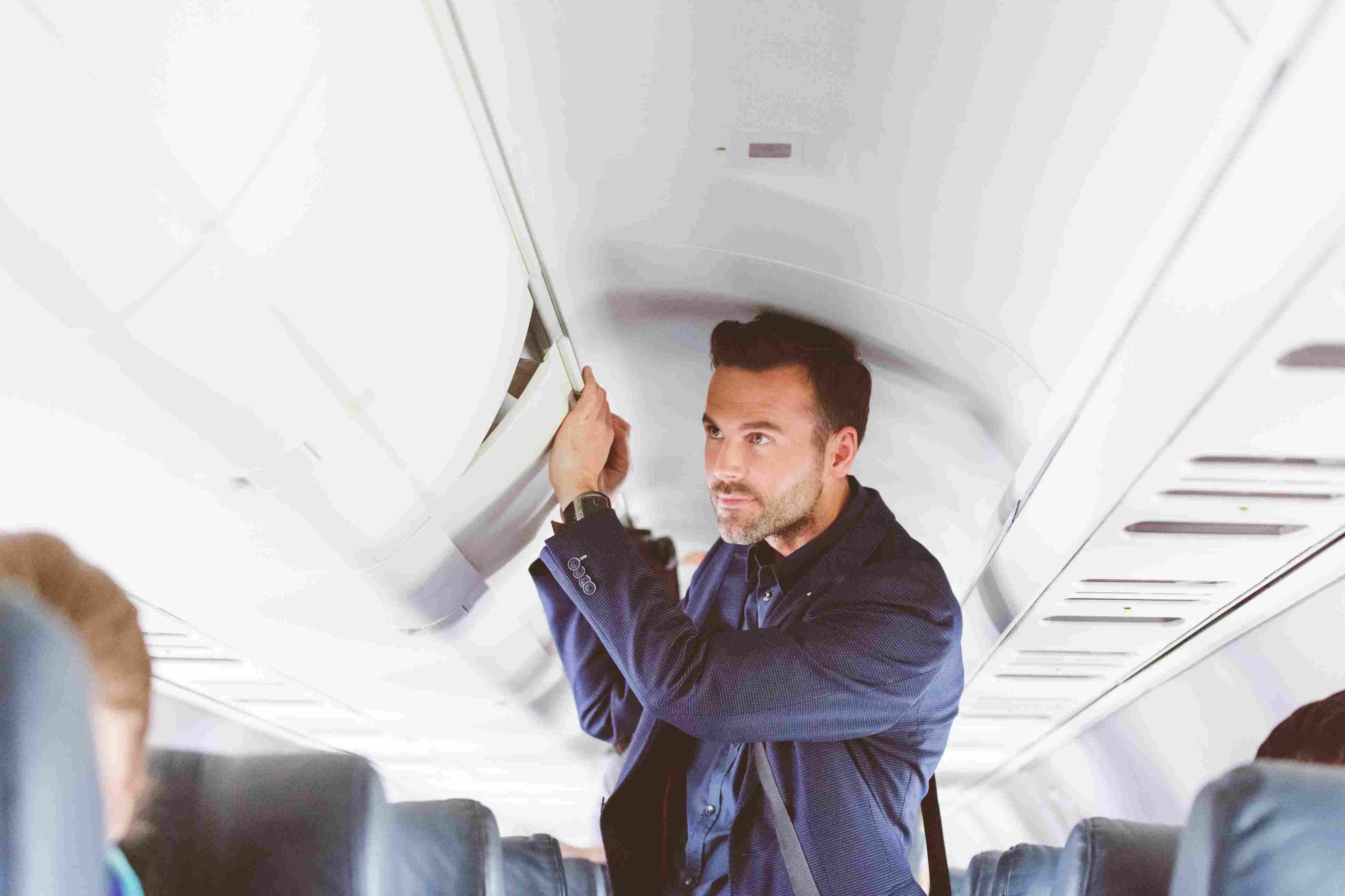 Man traveling by flight storing handbag in overhead locker