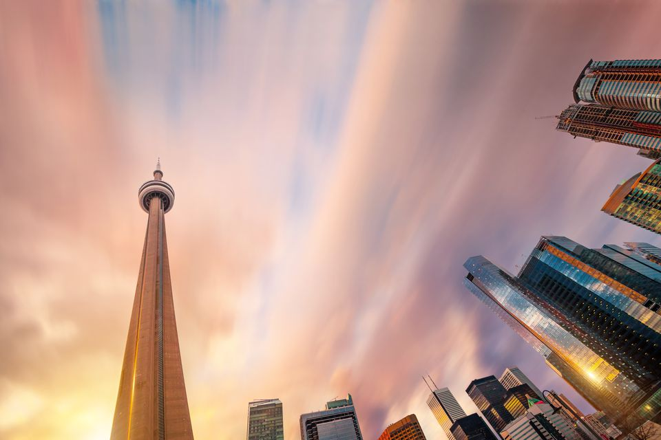 CN Tower rising straight up against modern corporate skyscrapers in downtown Toronto at sunset