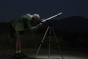 Mature man looking through telescope