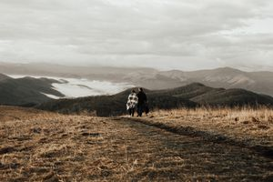 Two campers walking towards mountains