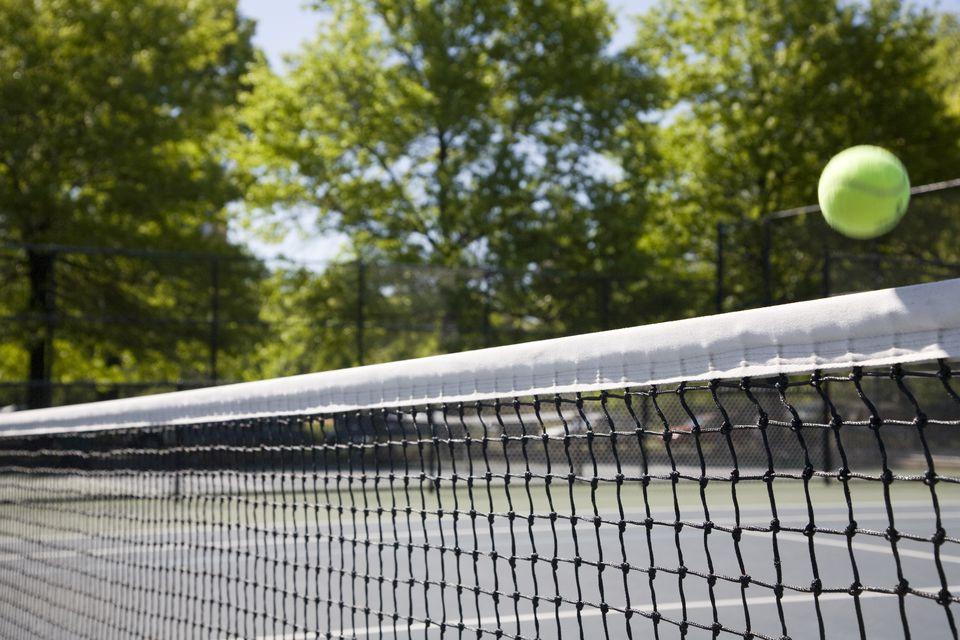 Una pelota de tenis volando sobre una red.