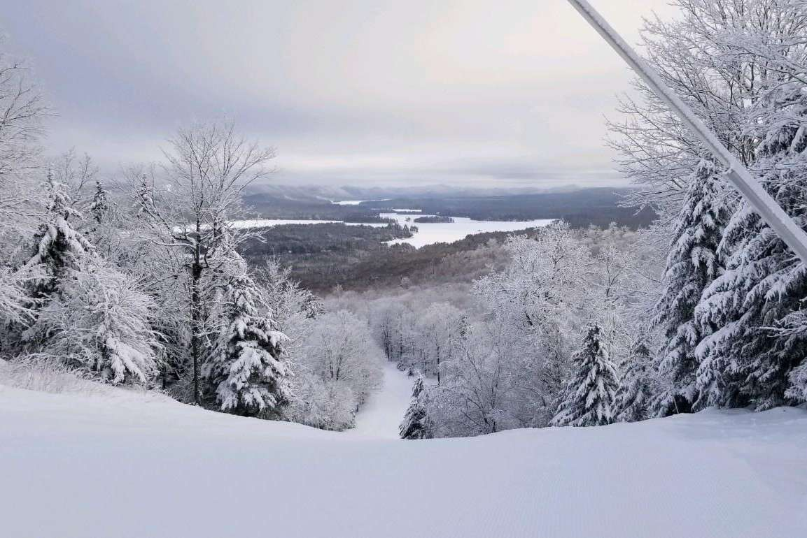 View of a ski run in New York with a river in the far distance