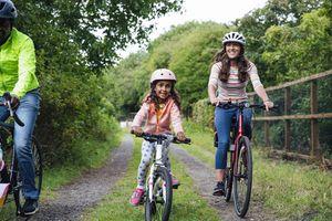 Family riding their bikes around a public park