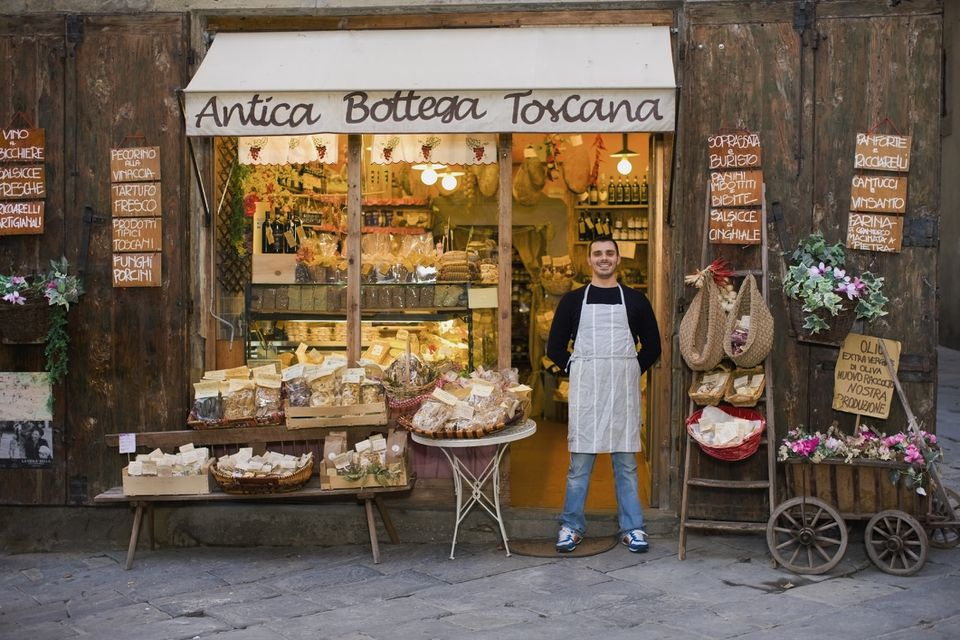 Owner in front of food bottega in Tuscany