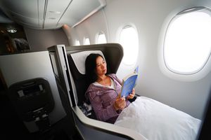 A woman relaxing on a first class flight with a book