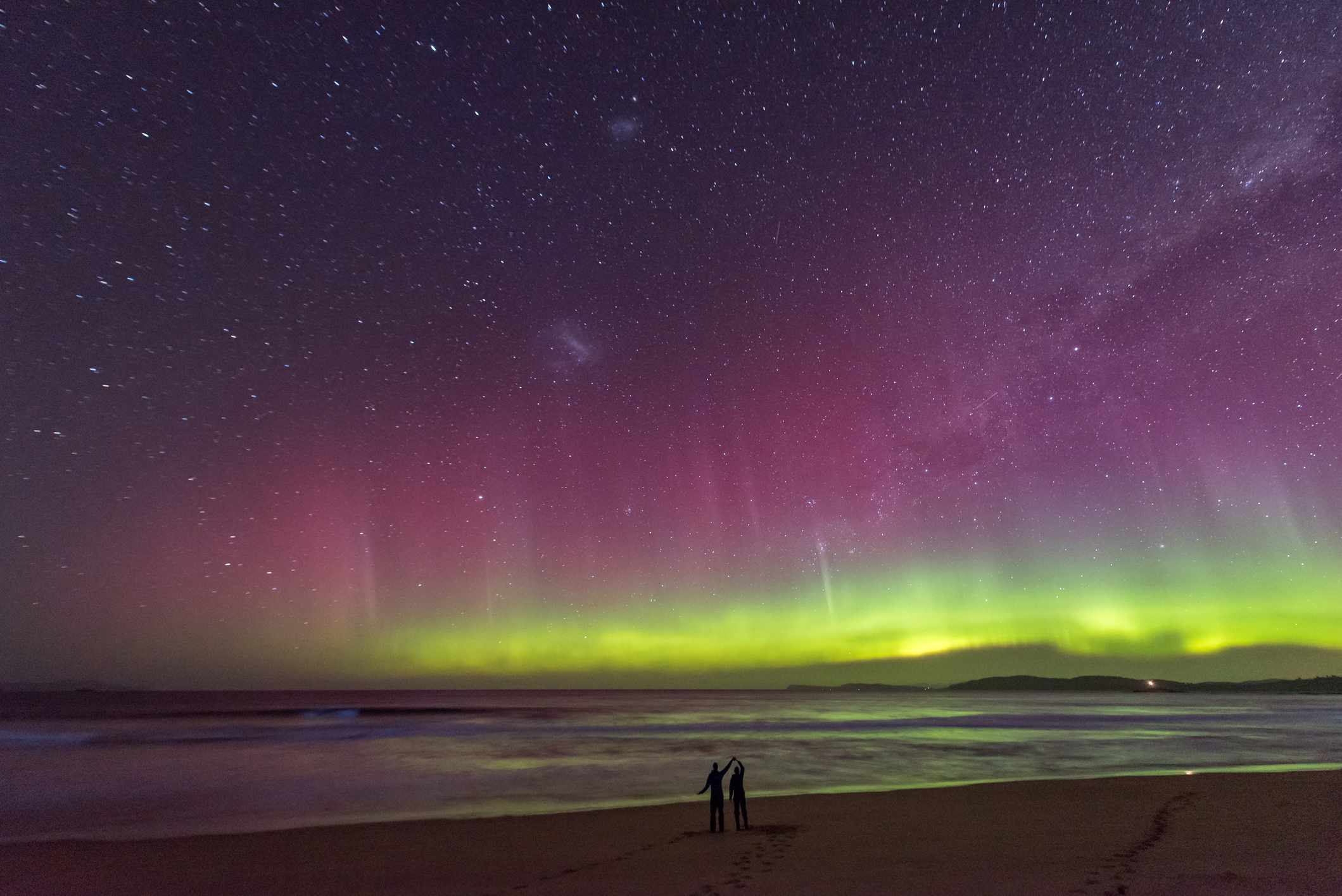 Couple standing on a beach under purple and green light