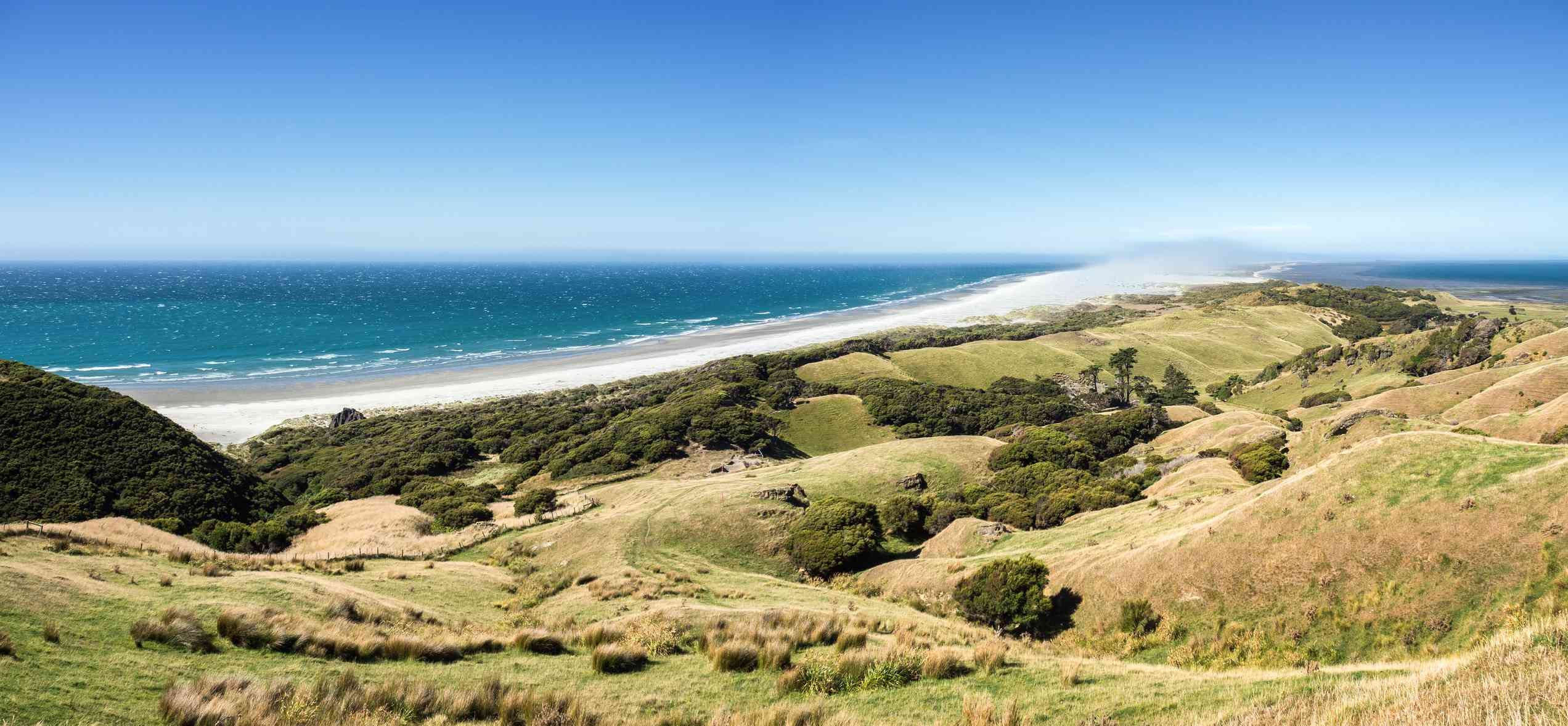 grassy hills and long whitesand beach with sea beyond