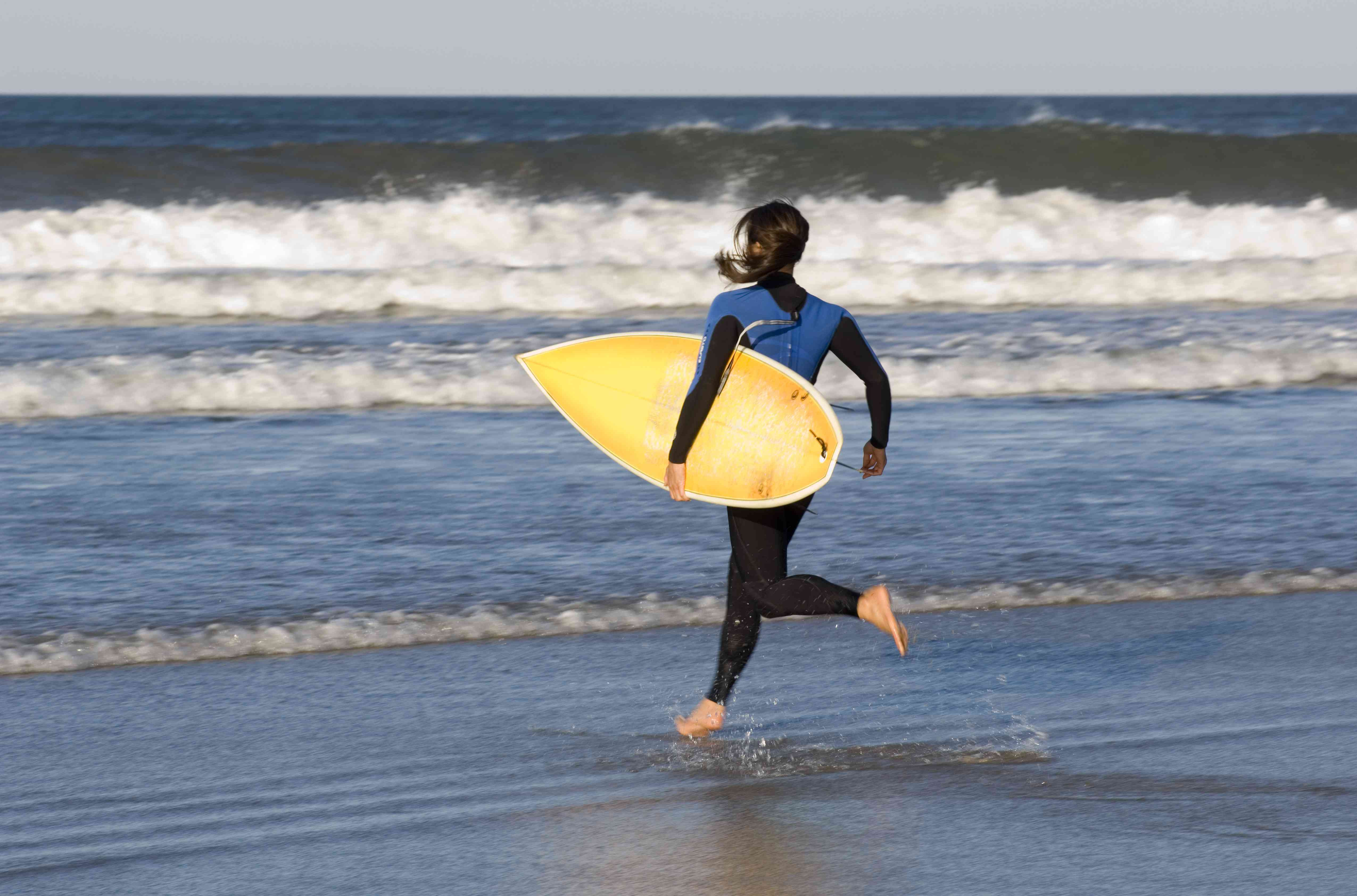 Female surfer running with surfboard