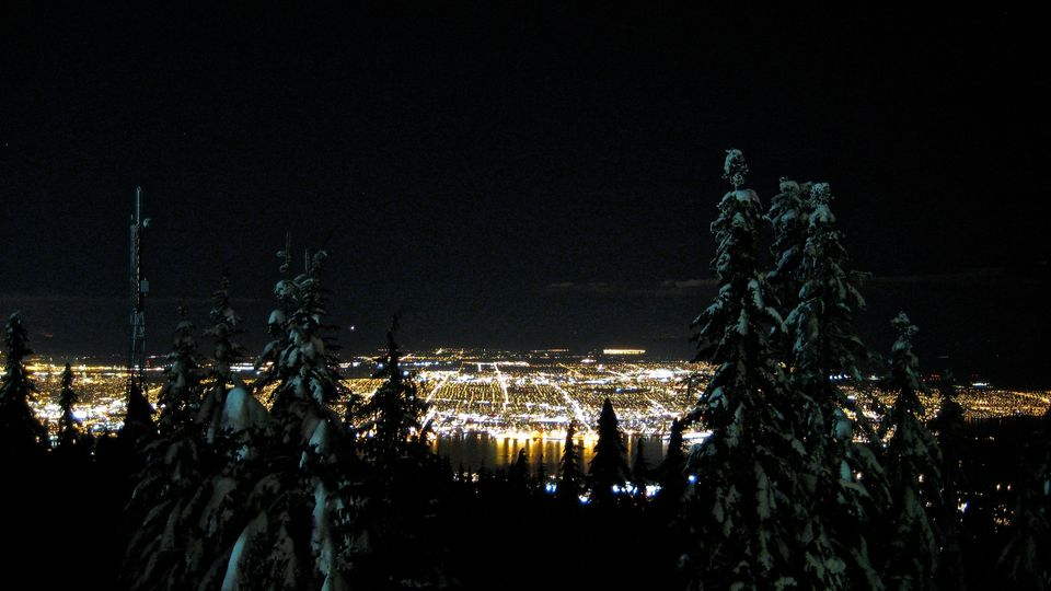 Illuminated Cityscape At Night Viewed From Mountain