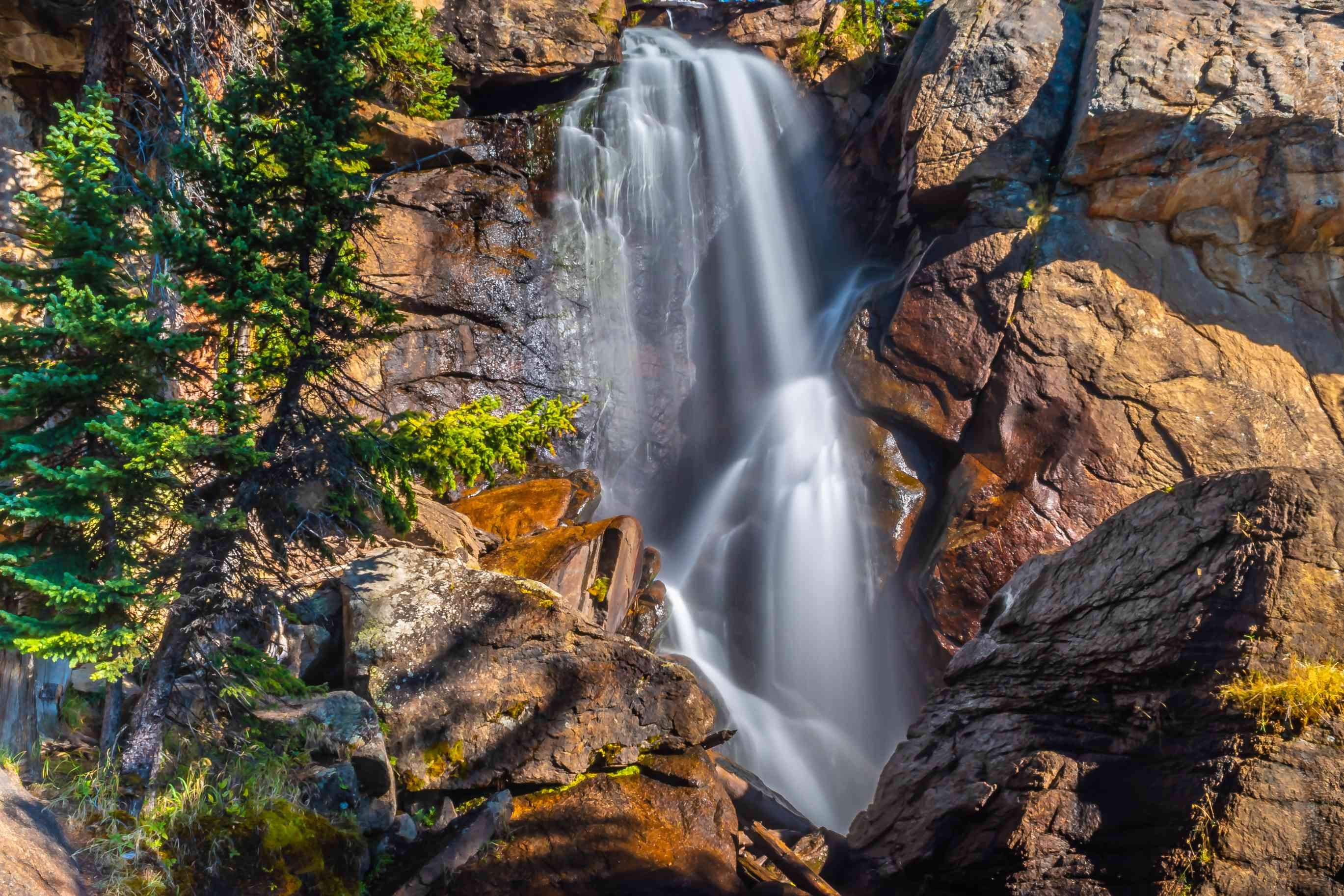 long exposure image of a waterfall going over brown rocks
