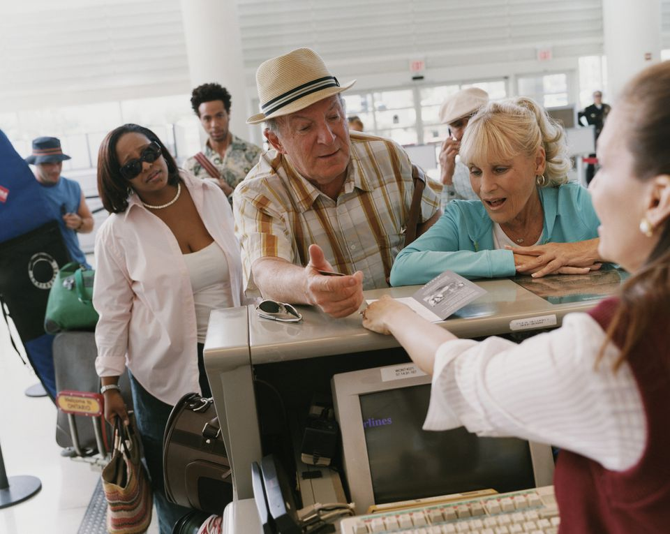 Senior couple talking to an airline ticket agent at an airport