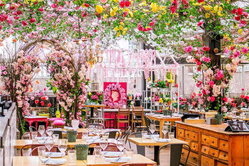 Bright, airy room covered in flowers with wooden tables