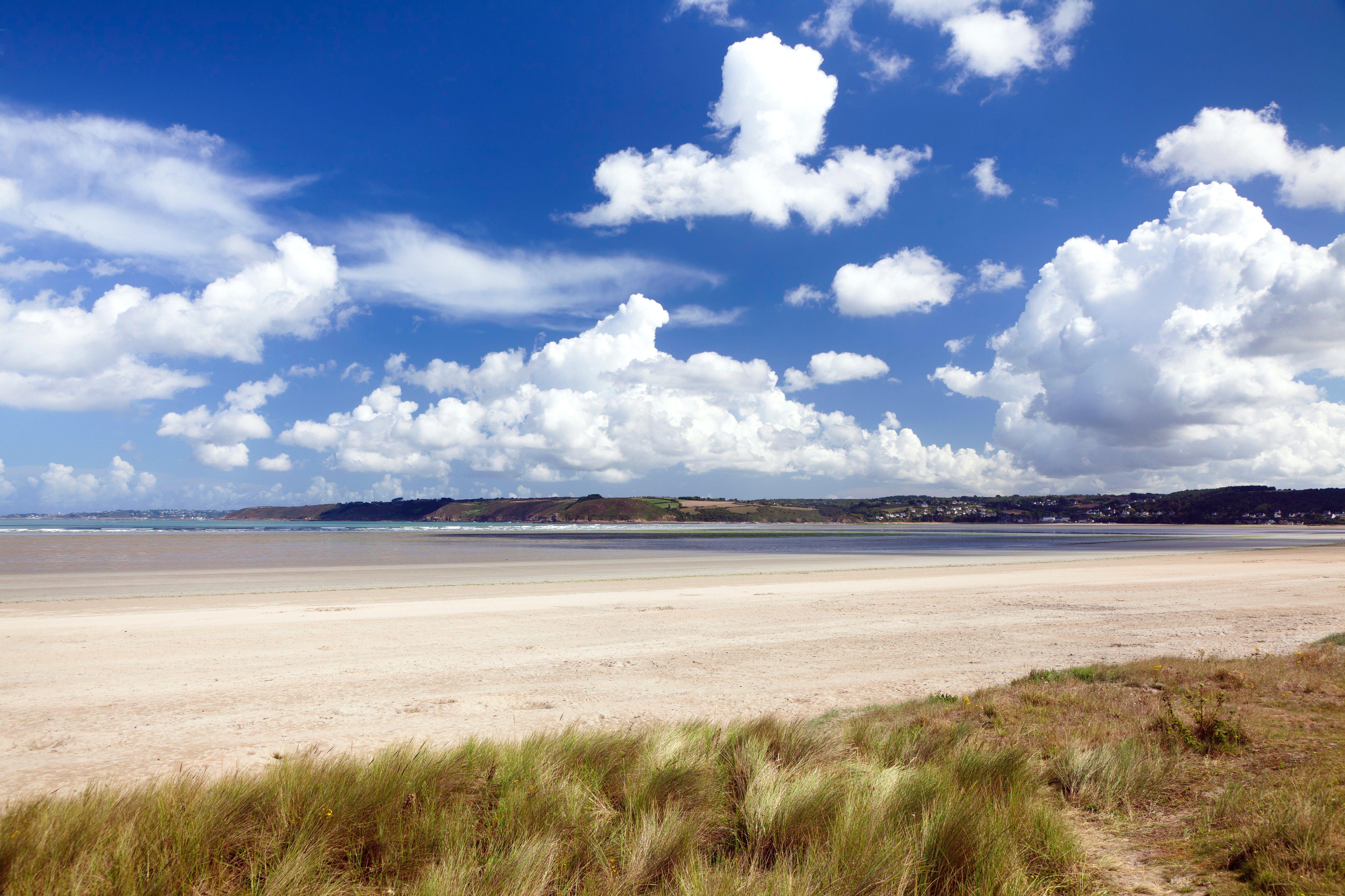 Dunes and cumulus clouds along the water, Baie de Lannion, Cote de Granit Rose, Cotes d'Armor