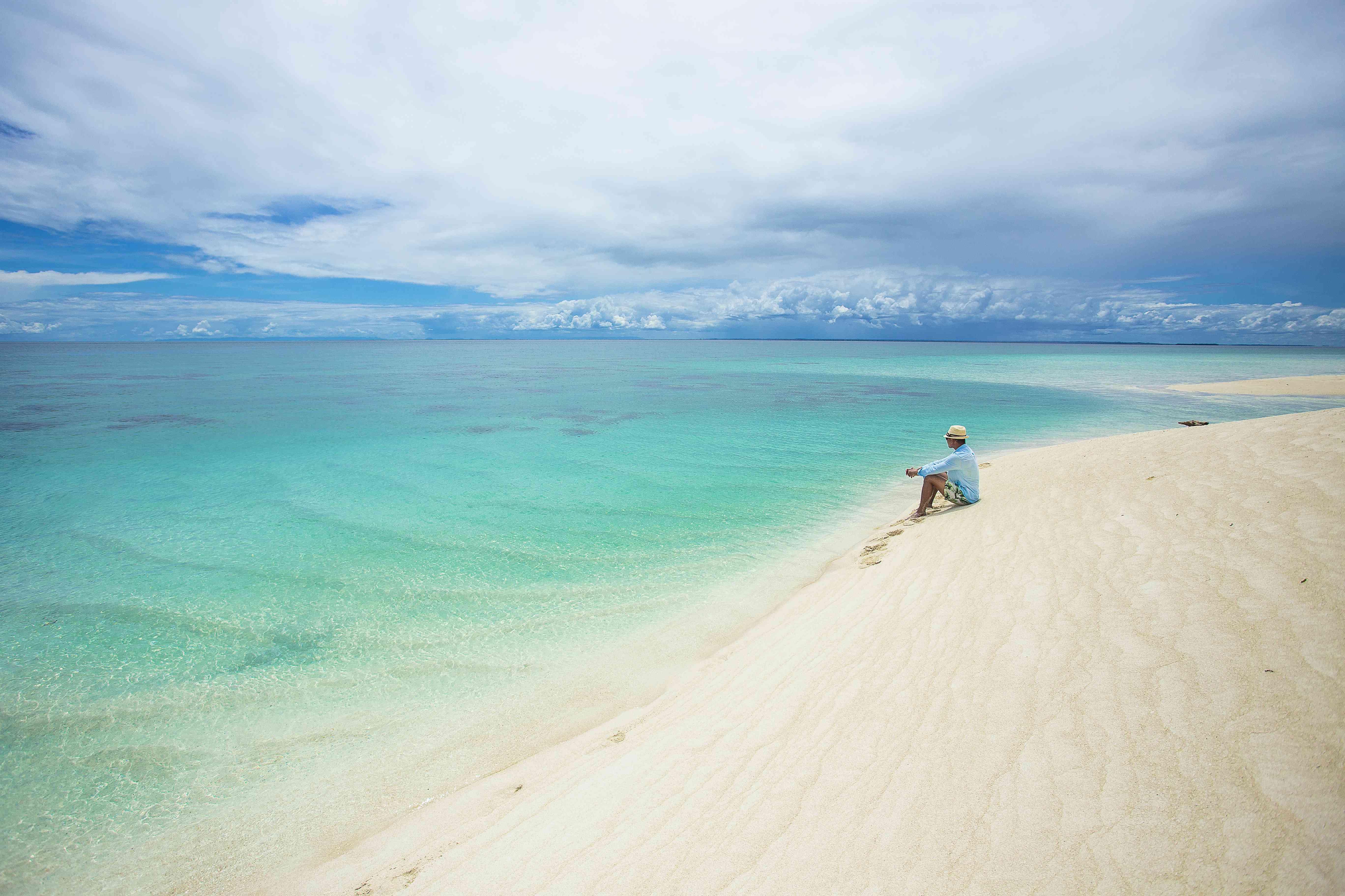 Man sitting on a beach on Derawan Island, Borneo