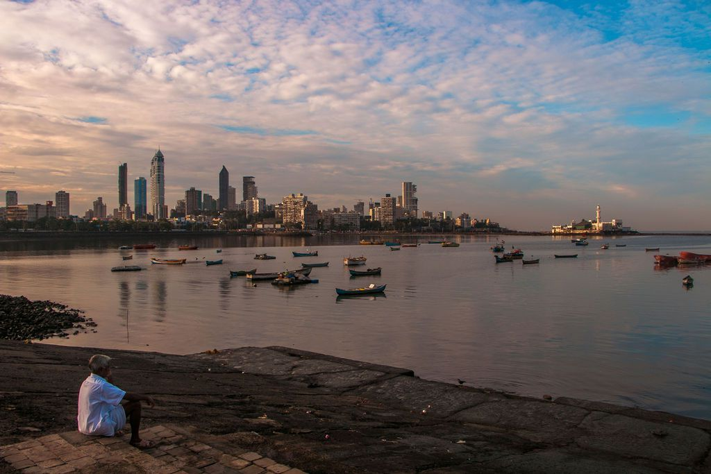 A man sitting on the banks of the water overlooking Mumbai at sunset