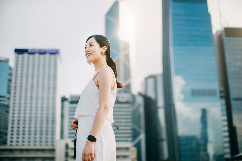Confident young Asian businesswoman looking up to sky while standing against urban scene in financial district of Hong Kong