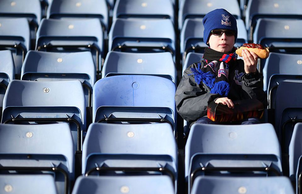 A Crystal Palace fan eats a hot dog before a game at Selhurst Park