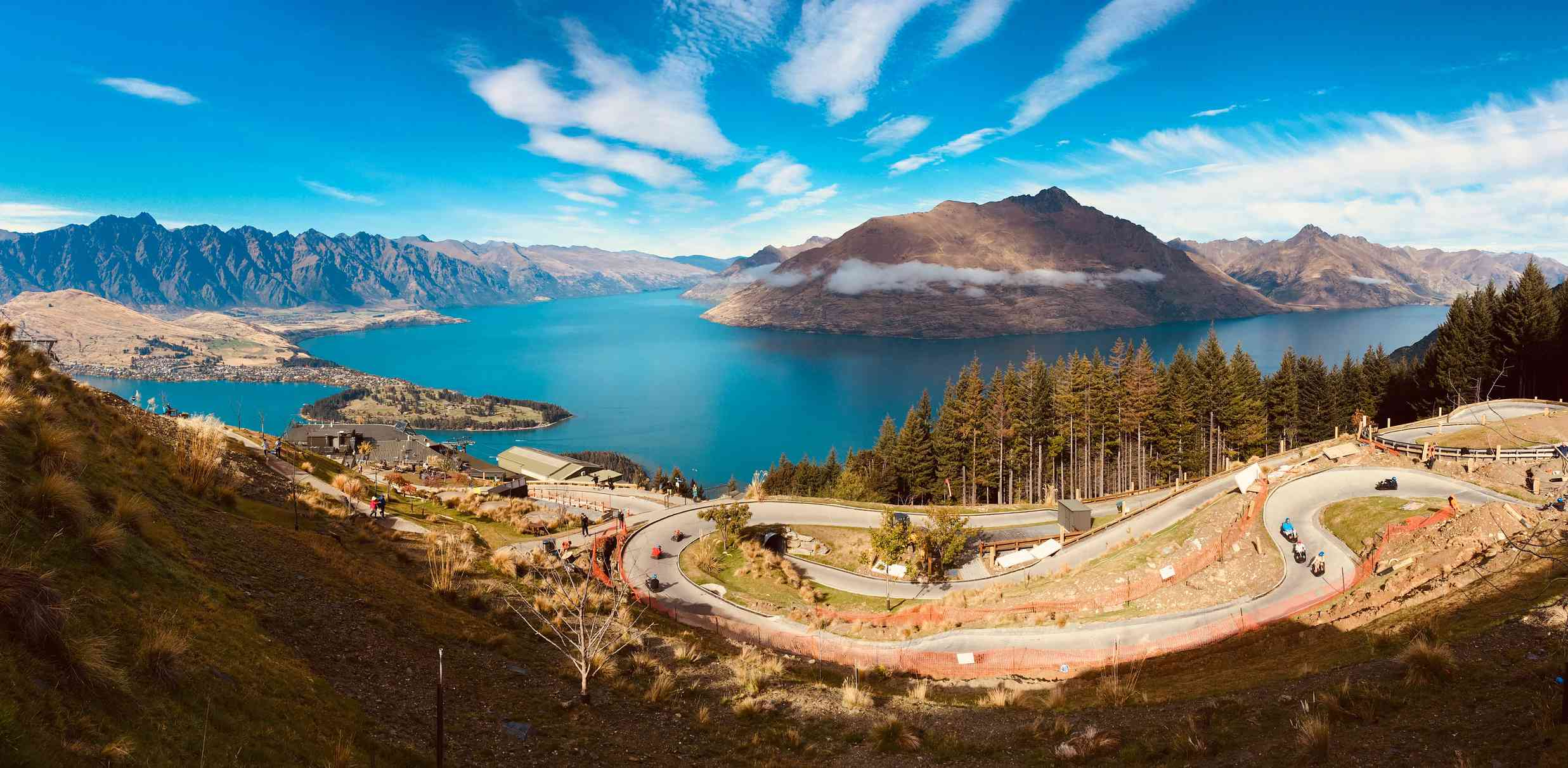 luge track winding down a hill with lake, mountains and blue sky in background