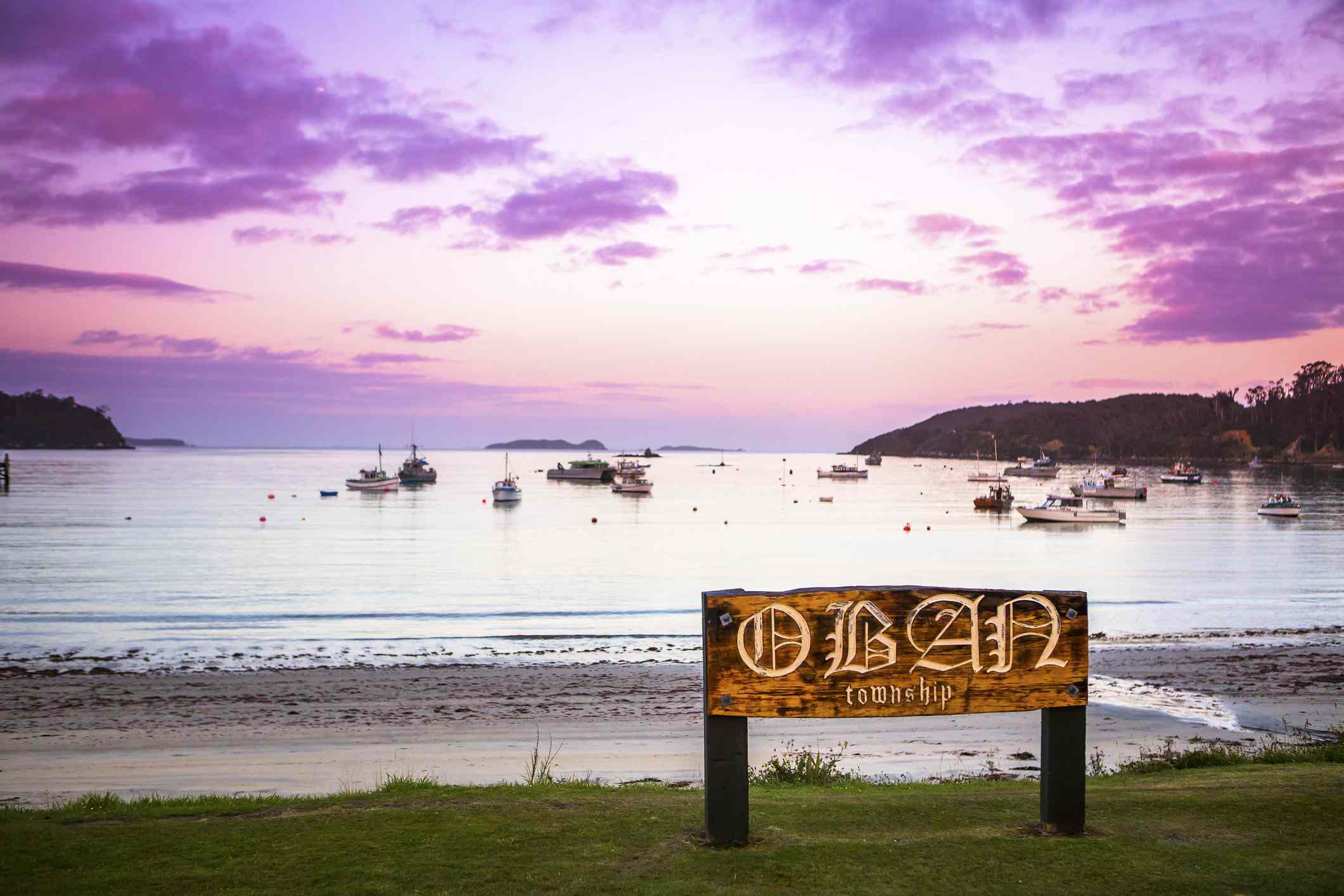 boats in the water with a pink sky overhead. In the foreground there is a road and an aged sign that says OBAN township
