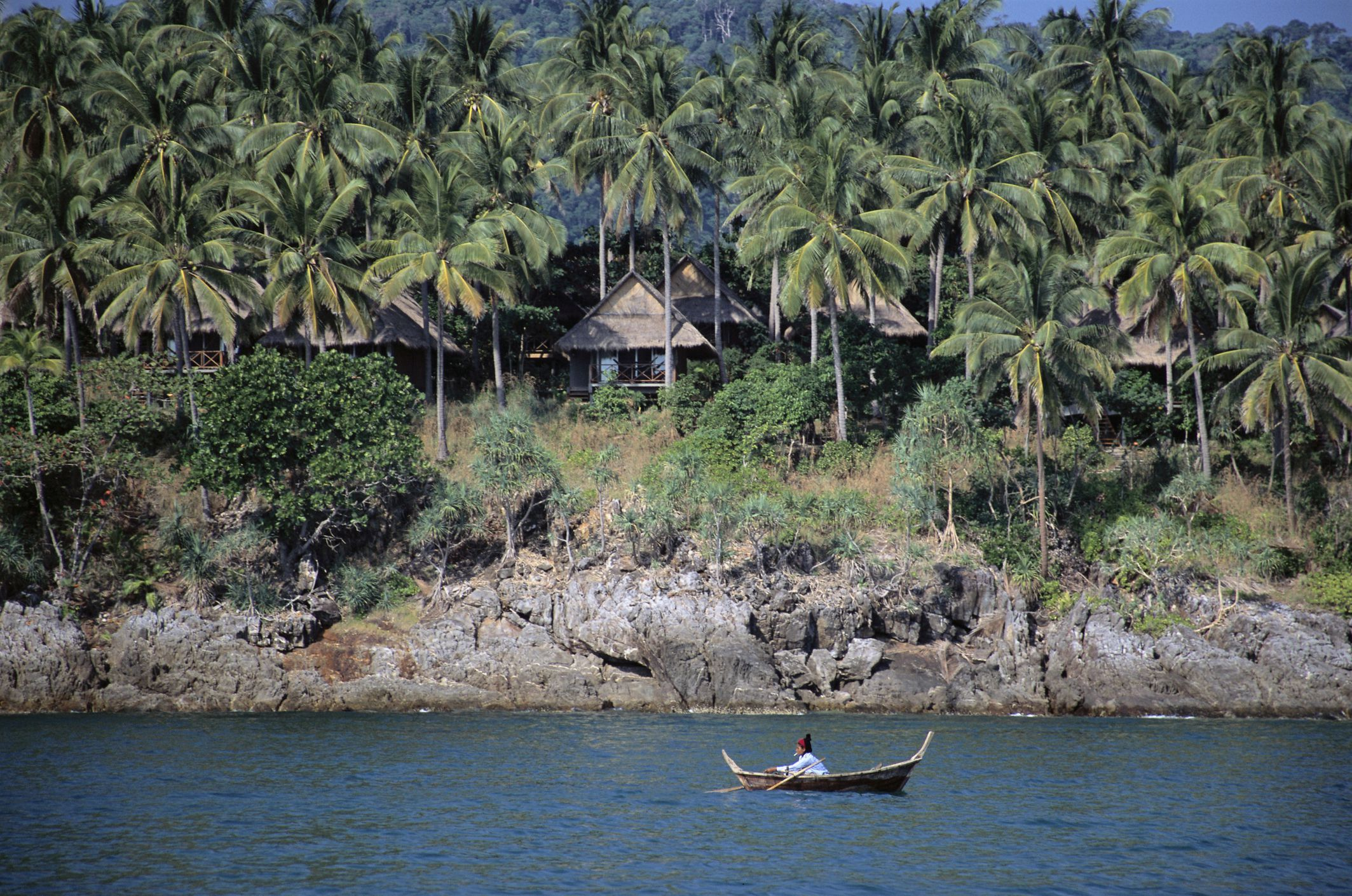 A fisherman rows a small boat below bungalows set on a rocky cliff, Koh Lanta