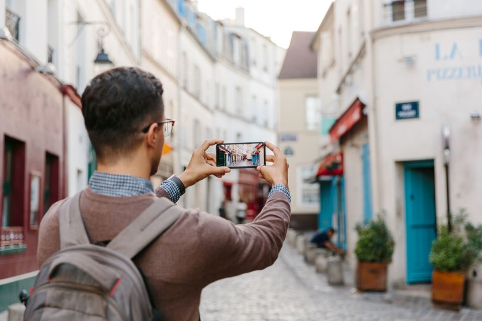Young man taking a photo of Montmartre street with his smartphone in Paris