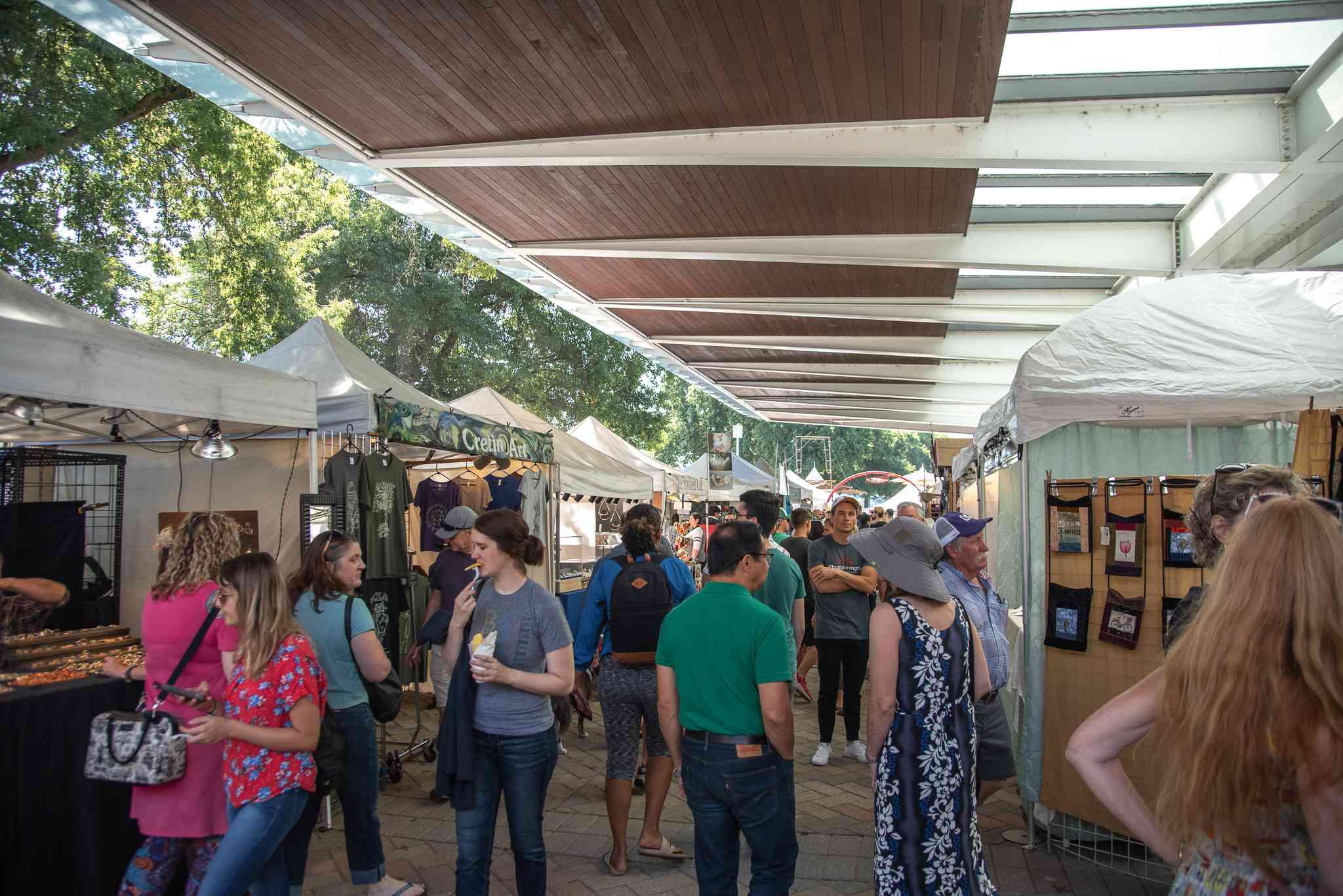 Gente deambulando por las filas de vendedores en el mercado del sábado